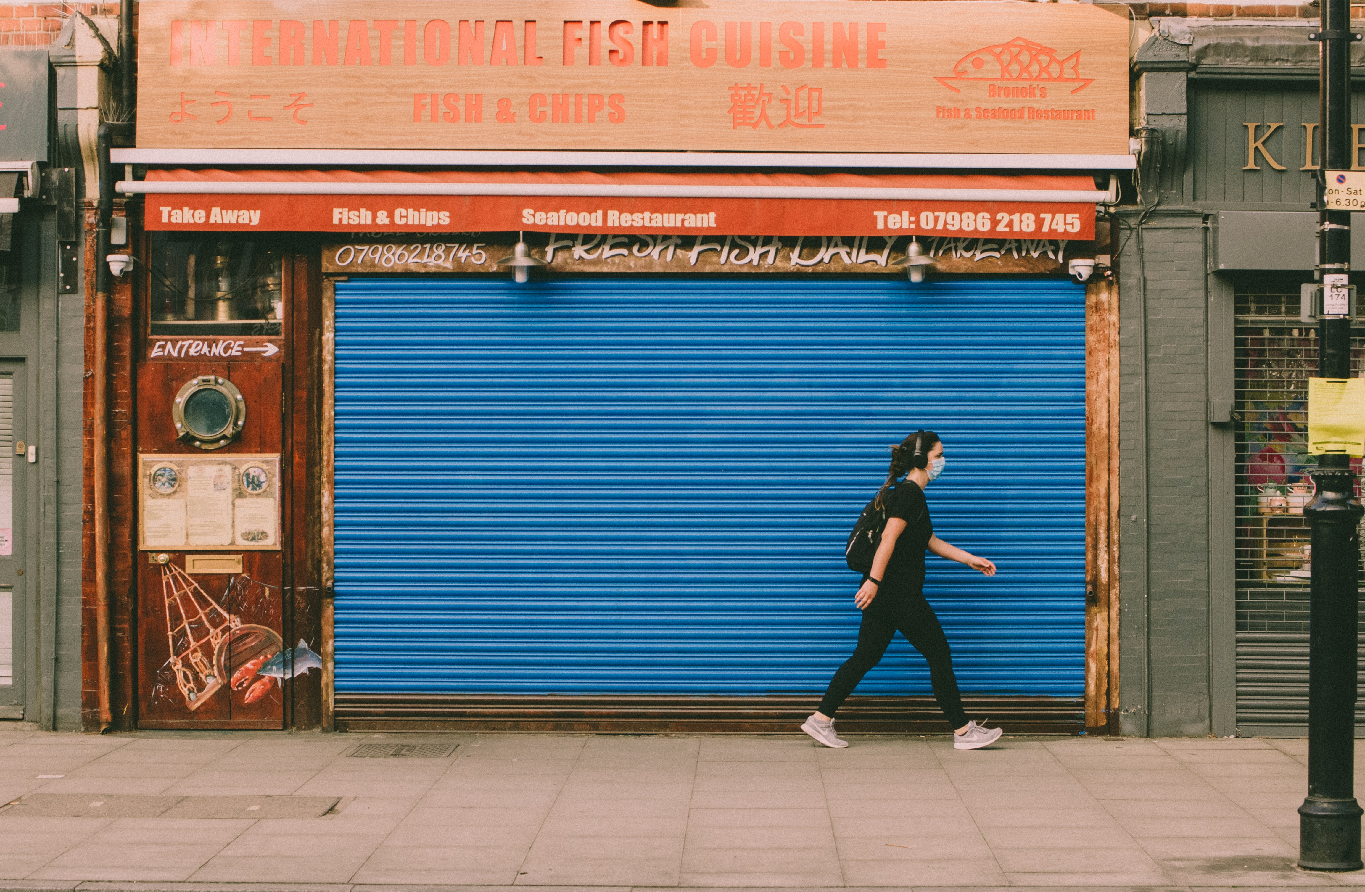 Woman walking past closed shop with face mask on.