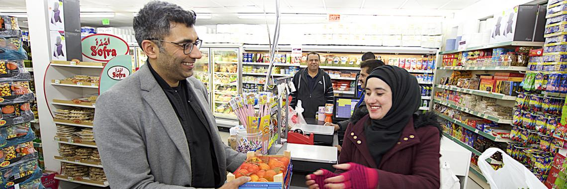Muslim checkout assistant serving a customer