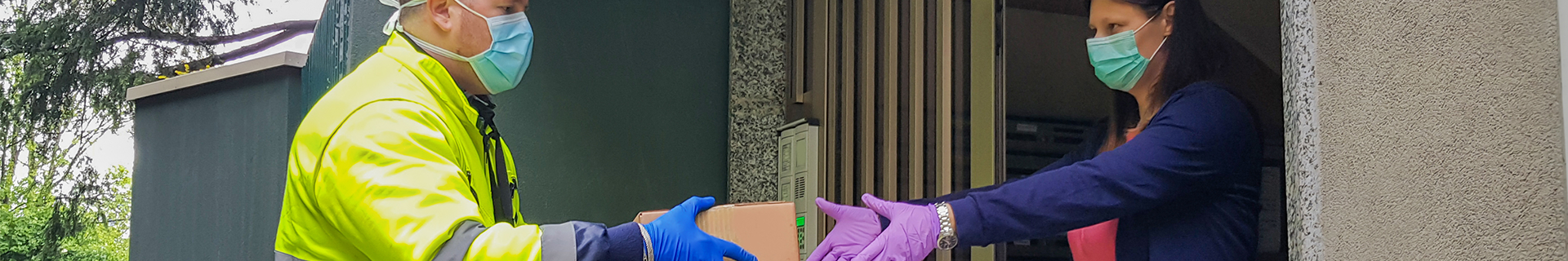 A woman in face mask and gloves takes a delivery of a box from a man also in face mask and gloves