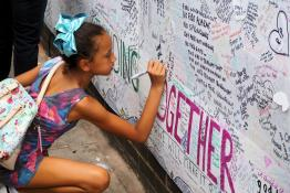 Girl writing on Grenfell memorial wall