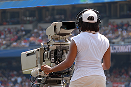 A camerawoman covers a tennis match