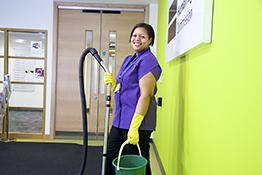 Cleaners' rights: female cleaner with vacuum cleaner and bucket