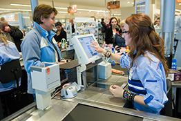 Man being served by a supermarket cashier