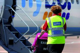 Wheelchair user receiving assistance to board a plane