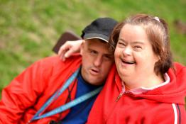 A young woman and man with Downs Syndrome hug and smile