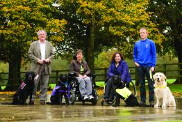 Group of four people, each with an assistance dog
