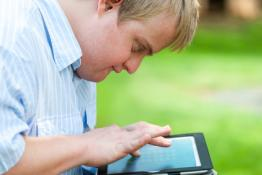 A man with Downs Syndrome searches for information on an iPad