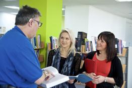 Hearing impaired man talking to two women in a library