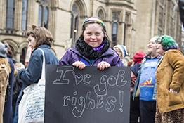 Disabled girls at an equality march, holding a sign saying 'I've got rights!'