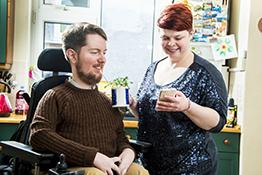 A disabled man in a wheelchair is helped by his carer