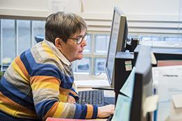 A woman sitting at a desk in an office, looking at a computer screen