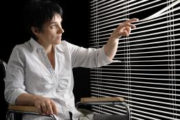 A woman in a wheelchair looks through her window blinds.