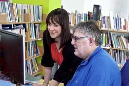 Hearing impaired man works with a female colleague in an office