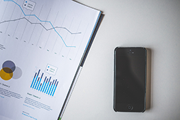 A smartphone next to a report showing data tables and graphs