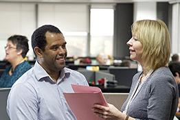 Two colleagues of different ethnicities talking in an office