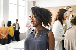 Smiling woman networking at an event. Copyright: shutterstock.com/rawpixel
