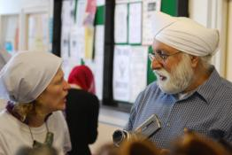 A man and woman talking in a community centre