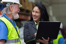 A woman with a laptop talks to a man on a construction site
