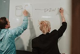A man and woman write on a whiteboard