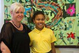Teacher and transgender student standing in front of colourful mural