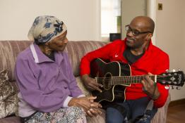 man with mother playing guitar