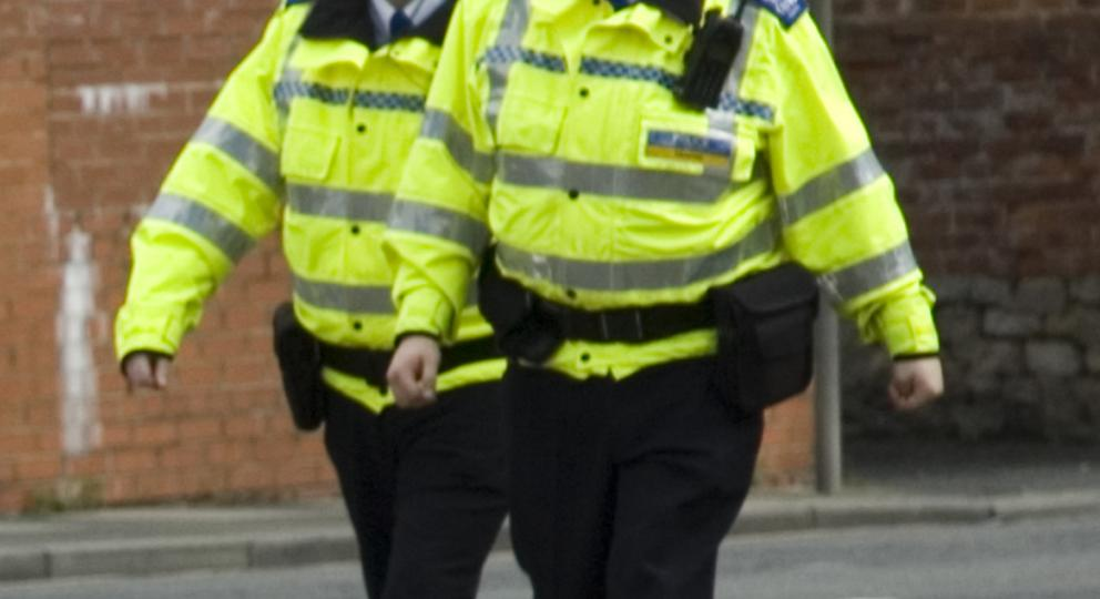 Two police officers in the street walking towards a disabled person in an electric wheelchair