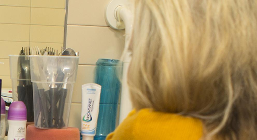 Sophie, a wheelchair user, brushes her hair looking in the mirror in her bathroom