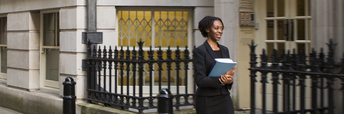 A woman walking along a street with legal papers in her hand